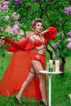 Девушка в красивом красном нижнем белье на природе.