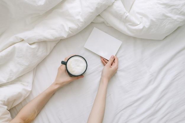 카드와 컵 커피를 들고 침대에서 소녀. 컨셉 사진 평면도