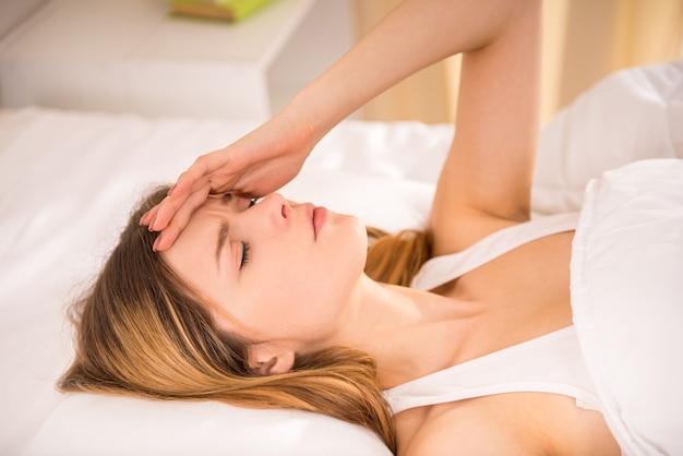 침대에서 여자가 거짓말을하고 그녀의 머리를 보유하고있다.