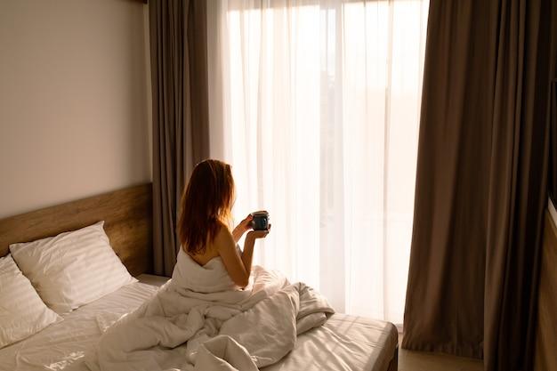 コーヒーとコーヒーの朝のベッドの女の子ベッドのお茶と白いベッドの女の子を目覚めさせるコーヒーとリネン