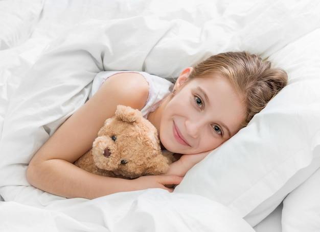 Девушка в постели с плюшевым мишкой, засыпая Premium Фотографии