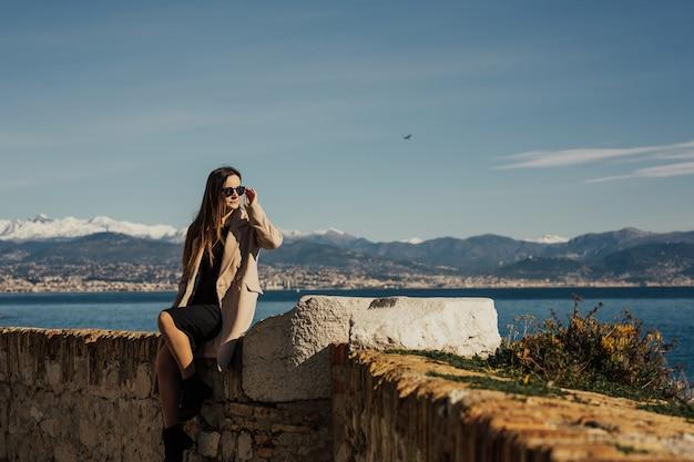 有名な地中海のアンティーブ港を訪れるメガネをかけたベージュのコートと黒のドレスを着た女の子。