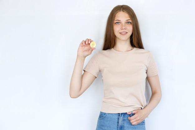 灰色の背景にビットコインとベージュのtシャツの女の子
