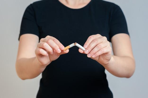 黒い服を着た女の子がタバコを壊します。灰色の背景に。禁煙のコンセプト