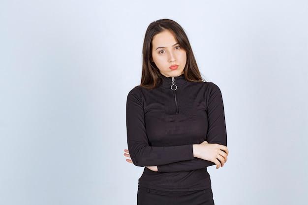 반응없이 전문적이고 중립적 인 포즈를 취하는 검은 옷을 입은 소녀.