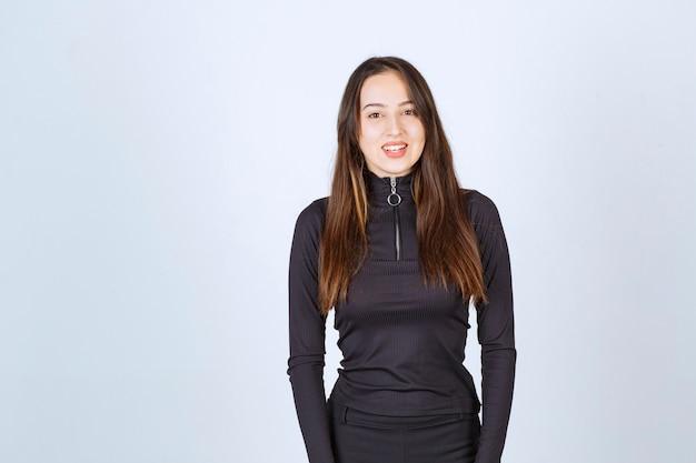 Девушка в черной одежде без реакции принимает профессиональные и нейтральные позы.