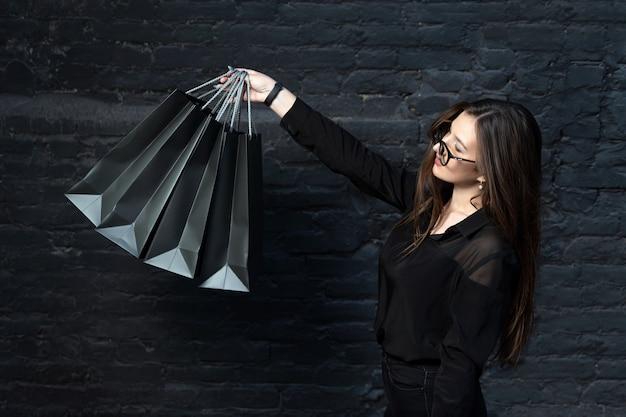 검은 옷을 입은 소녀는 검은 벽돌 벽 배경에 종이 쇼핑백을 보유하고 있습니다. 검은 금요일.