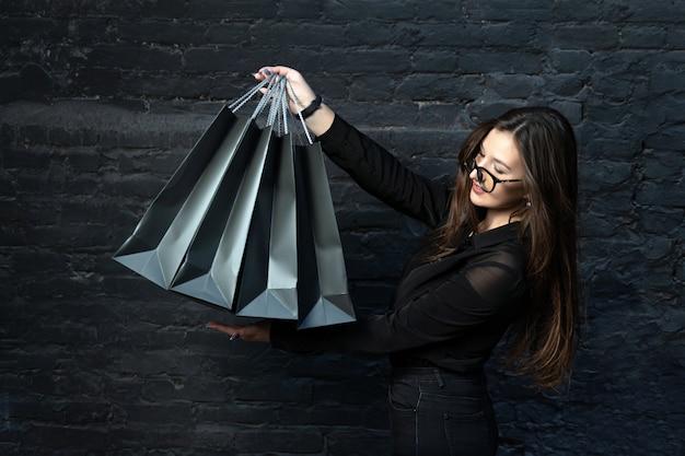 黒い服を着た女の子が黒いレンガの壁に紙の買い物袋を持っています