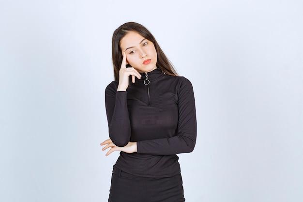 검은 옷을 입은 소녀는 사려 깊고 의심스러워 보입니다.