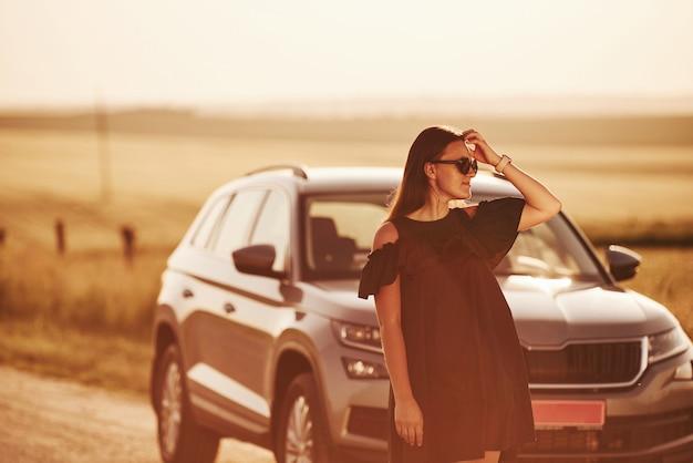 야외에서 현대 럭셔리 자동차 근처 포즈 검은 옷을 입은 소녀