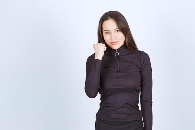 Девушка в черной одежде, показывая мышцы кулака и рук.