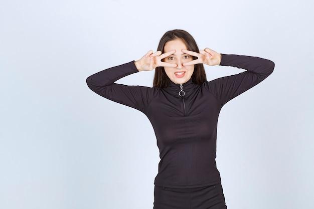 平和と友情のサインを示す黒い服を着た女の子。