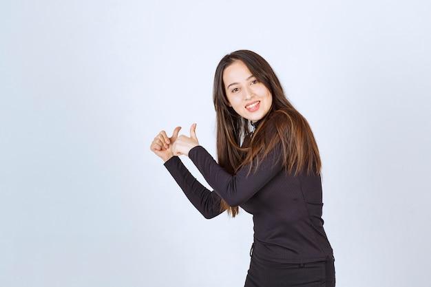 親指を立てるサインを示す黒い服を着た女の子。