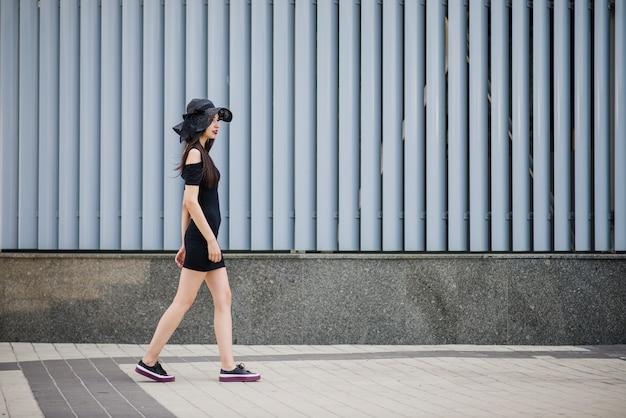 Девушка в черном платье, выходящая на улицу