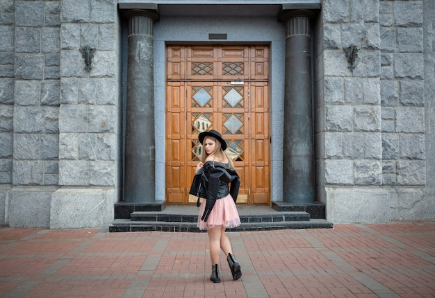 旧市街の通りでポーズをとって黒い帽子の少女