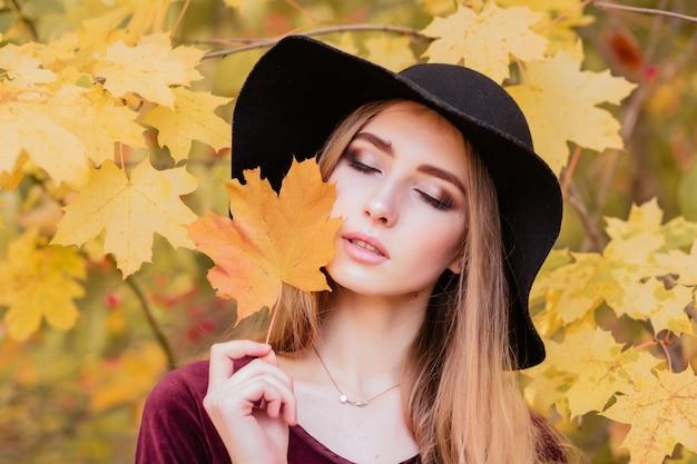 秋に黄色の葉と黒い帽子の少女
