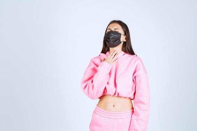 彼女の胸を指して咳をしている黒いマスクの女の子。