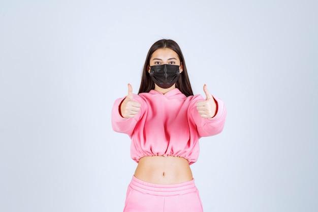 親指を立てるサインを示す黒いマスクの女の子。