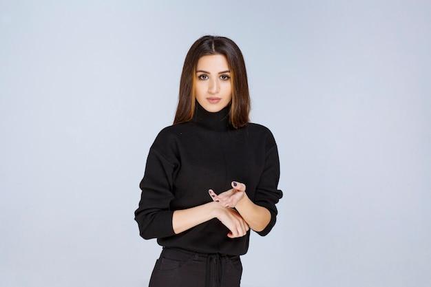 ソーシャルメディアのカバー写真に魅力的なポーズを与える黒いシャツの女の子。高品質の写真