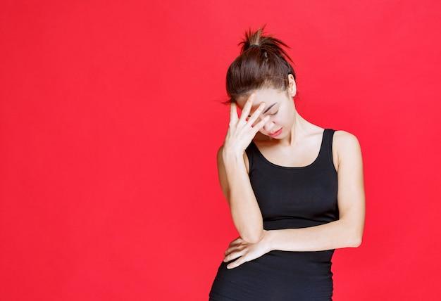 검은 셔츠를 입은 소녀는 피곤하고 졸립니다. 고품질 사진