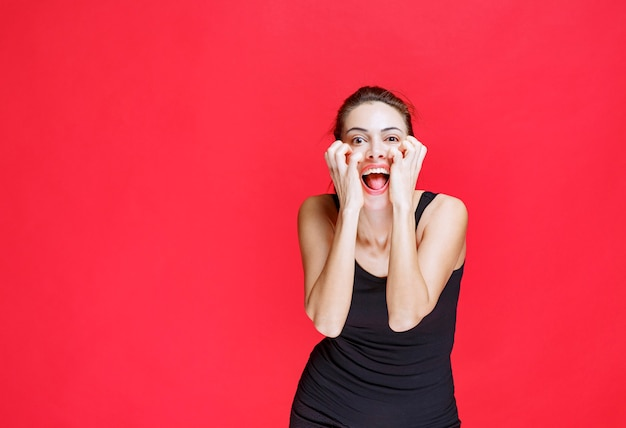 愚か者として大声で笑っている黒いシャツの女の子。高品質の写真