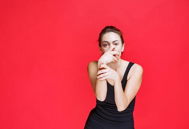 彼女の指を横切って見ている黒いシャツの女の子。高品質の写真