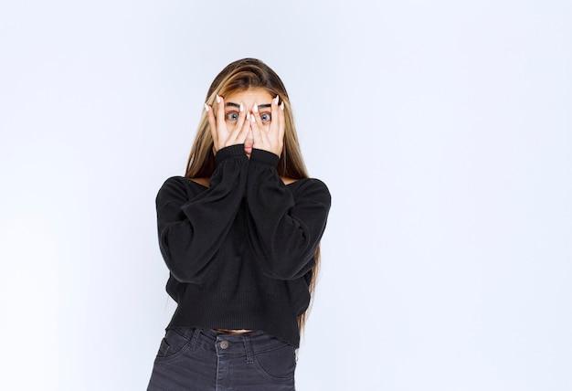 指を通して見ている黒いシャツの女の子。