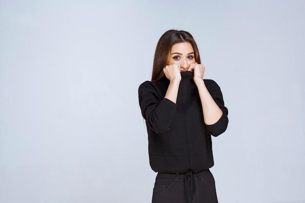 Девушка в черной рубашке выглядит взволнованной и напуганной. фото высокого качества