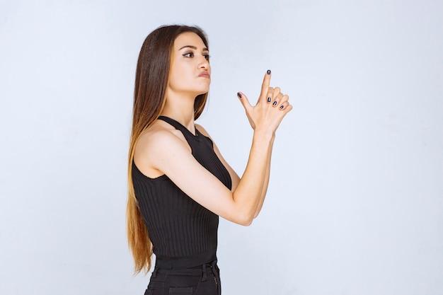 손으로 총 기호를 만드는 검은 셔츠에 소녀입니다.