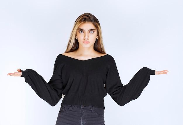손을 열고 어깨를 으쓱하는 검은 셔츠에 소녀입니다.