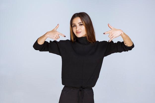 자신을 가리키는 검은 셔츠에 소녀입니다. 고품질 사진