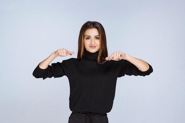 자신을 가리키는 검은 셔츠에 소녀입니다. 고품질 사진 무료 사진