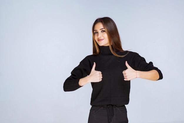 ポジティブな手のサインを示す黒いシャツの女の子。高品質の写真