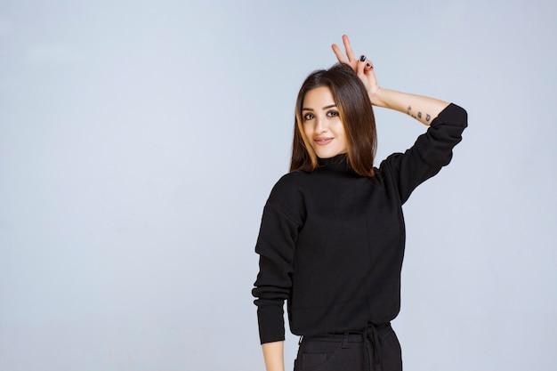 ウサギの耳のサインを示す黒いシャツの女の子。高品質の写真