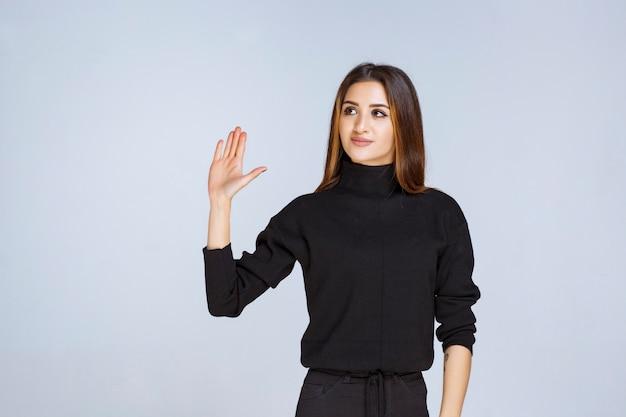 Девушка в черной рубашке останавливает и что-то предотвращает. фото высокого качества