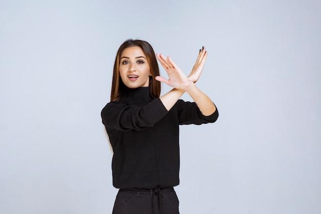 黒いシャツを着た女の子が何かを止めて防いでいます。高品質の写真