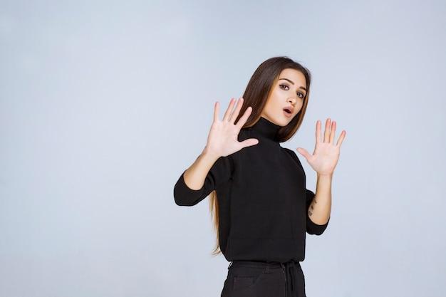 검은 셔츠에 소녀 중지 및 뭔가 방지. 고품질 사진 무료 사진