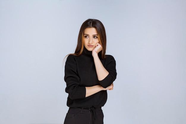 Девушка в черной рубашке думает и анализирует. фото высокого качества