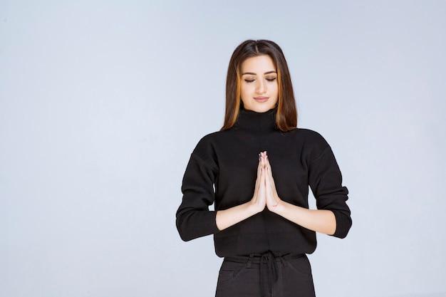 Девушка в черной рубашке, объединив руки и молясь. фото высокого качества