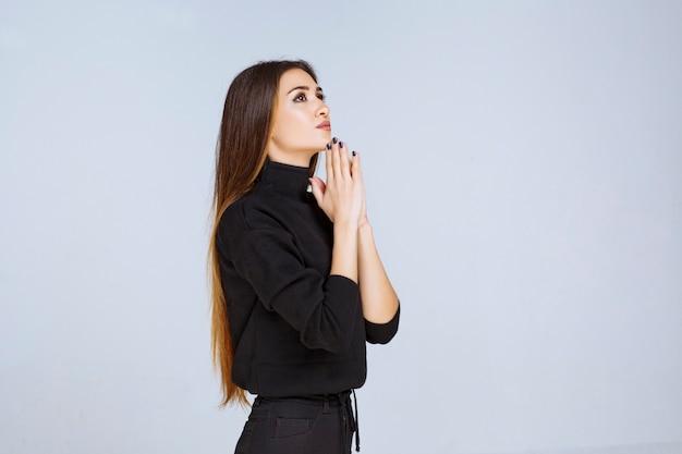 黒のシャツを着た女の子が両手を合わせて祈っています。高品質の写真