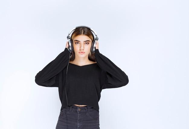 헤드폰을 끼고 음악을 듣고 있는 검은 셔츠를 입은 소녀. 고품질 사진