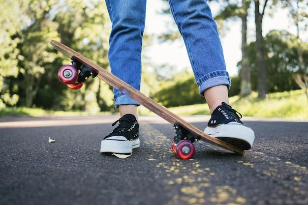 スケート ボードでアスファルトの道路に立っている黒い靴の女の子。