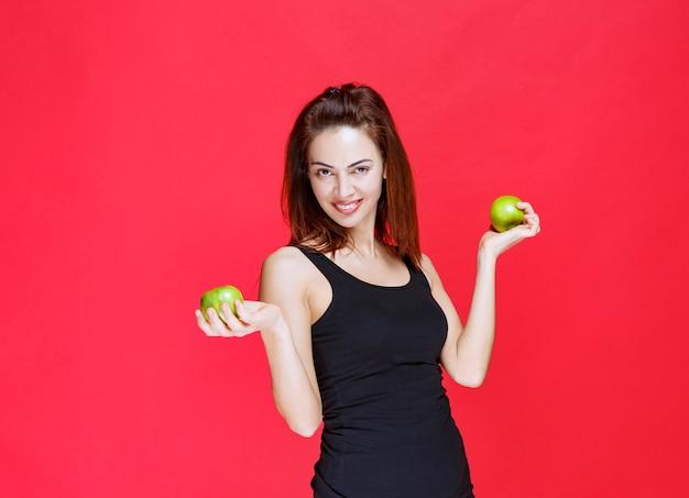 Девушка в черной майке держит зеленые яблоки.