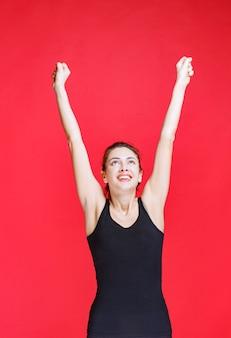 Девушка в черной майке стоит на красной стене и поднимает руки.