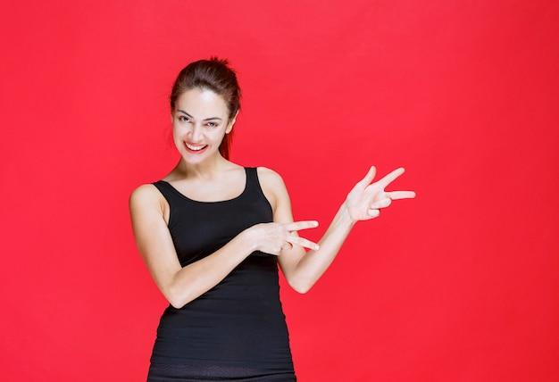 빨간 벽에 서서 오른쪽을 보여주는 검은색 외투를 입은 소녀.