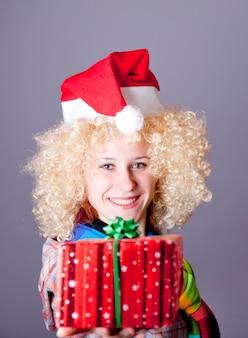 金髪のかつらとクリスマスの帽子の女の子は贈り物を示しています。スタジオショット。