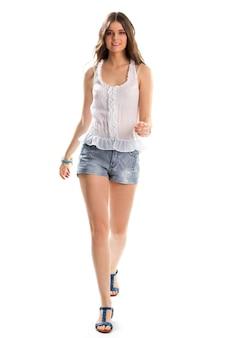 블라우스를 입은 소녀가 걷고 있습니다. 짧은 반바지와 샌들. 여름 의류의 심플한 디자인. 가벼움, 아름다움, 편안함.