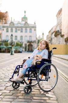 Девушка в голубом платье в инвалидной коляске на улице в городе.