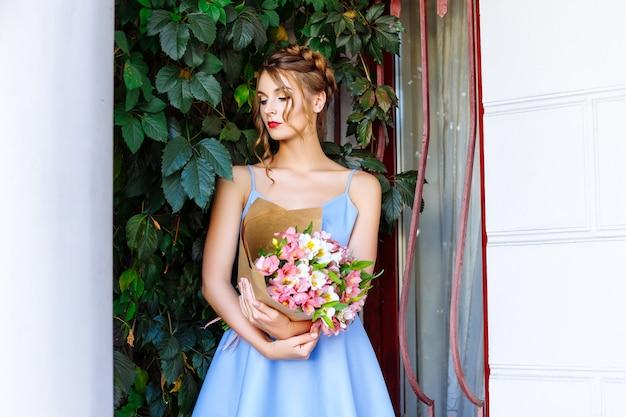 Девушка в голубом платье с букетом цветов на улице