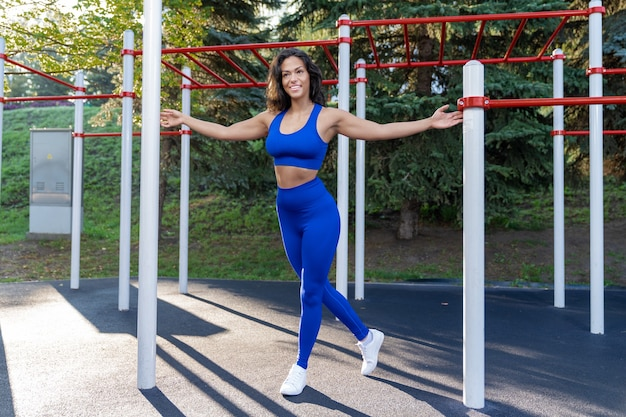青いフィットネス服の女の子は、屋外のスポーツグラウンドで動作します